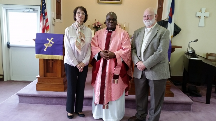 Father Pothin standing with two parishioners